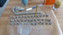 In die Tonstückchen werden mit einem nassen Bleistift Vertiefungen gedrückt